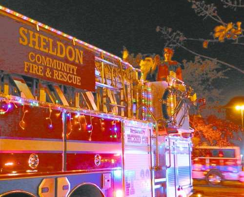 SANTA and his Elf helper arrived on a Sheldon Fire Department ladder truck, decorated for the Holiday Season with lights and Christmas greetings.