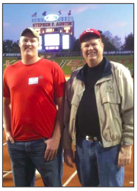Cody Stephens in a red t-shirt with his father, Scott Stephens, in a football field prior to Cody's sudden death.