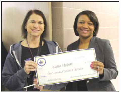 Pictured are Channelview High School science teacher Karen He- bert is presented with a $5,000 In- novative Teaching Grant by Chan- nelview ISD Education Foundation President Sholanda Dawkins during the Foundation's Surprise Patrol on March 7.