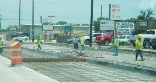 CONSTRUCTION WORKERS FROM ALLGOOD CONSTRUCTION prepare to pour concrete in a third new lane of the rebuilt Freeport Drive. Also being installed are new storm sewers and drains, and curbs and sidewalks.