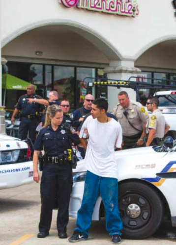 DEPUTIES ARREST the second suspect in front of the GameStop store on Wallisville, the site of a robbery and shooting. (Photo by Juan DeLeon)