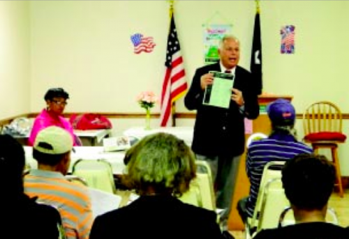 CONGRESSMAN GENE GREEN talks about his legislative program at the Town Hall Meeting in Galena Manor, and also about programs he sponsors in the community, such as Senior Citizens Forum, Immunization Day, Town Hall meetings, Job Fairs, Paying for College Workshop, and Service Academy workshops. At left is Galena Manor Civic Club president Mrs. Taggy Hall.