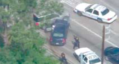 Houston Police fire on suspect after chase, as he reaches inside his car for an unknown object. (Photo courtesy KPRC)
