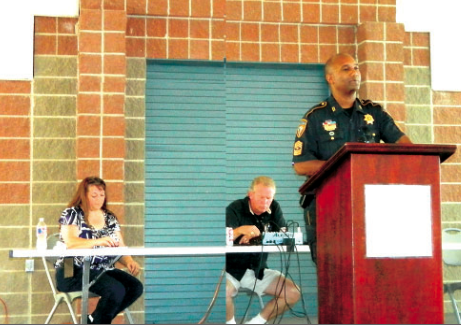 SGT. HALL of the Sheriff's office presents the main talk to the audience, about a Home Security Review to deter crimes in the neighborhood. Seated behind Hall are the organizers of the Crime Watch event, Julie Baer and David Baer.