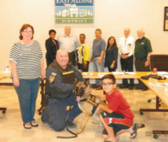 "EAST ALDINE BOARD MEMBERS pose with the K-9 that was purchased to honor the memory of fallen Deputy Jesse ""Trey"" Valdez III. Pictured in front are Valdez's mother, and HCSO Sgt. Chris Adolph with the dog Trey and Valdez's son, also Trey Valdez."