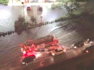 A HOUSTON FIRE TRUCK makes its way through high water Monday night, passing stranded cars parked on high ground. At top, flood waters reach parked cars at residences, and eventually entered the homes. (PHOTOS COURTESY KPRC)