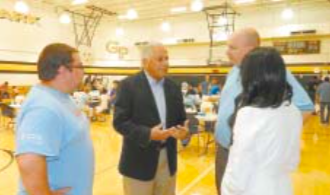 CONGRESSMAN GREEN confers with some of the Healthcare Providers that helped administer immunization shots, to the hundreds of children pictured in the background of the Galena Park High School gymnasium.