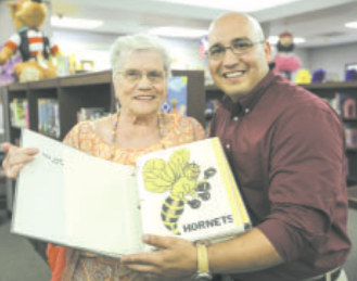 Woodland Acres Middle School Principal Lee Ramirez (right) enthusiastically accepts a scrapbook of the school from the 1940's from Pat (Bowles) Cooper (left).