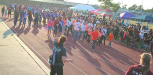 A large group of survivors wearing symbolic purple shirts makes the turn during the Survivor's Lap at the North Shore Ninth Grade Center.