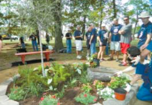 LYONDELLBASELL employees from the Channelview plant, including plant manager Todd Monette, at the center, cleaned and rebuilt a walking trail and memorial planting bed to remember and honor student James Brown, who died 10 years ago.